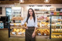 Woman owning bakery. Cheerful young woman wearing apron owning bakery feeling excited before starting work