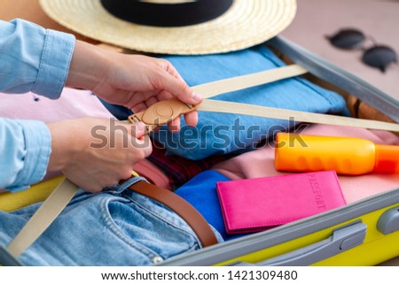 Woman packing a luggage at home for a new journey and travelling. Traveling suitcase for holiday travel and vacation  #1421309480
