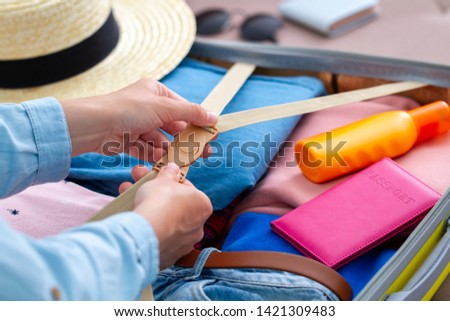 Woman packing a luggage at home for a new journey and travelling. Traveling suitcase for holiday travel and vacation  #1421309483