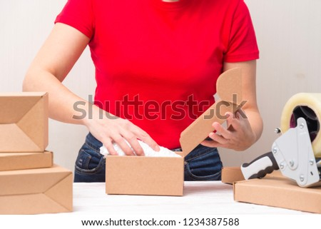 Woman packing cardboard boxes , picking and putting products
