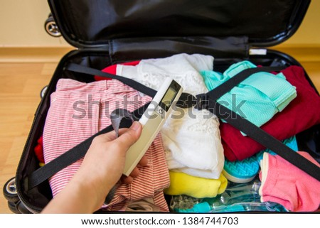 Woman packing digital luggage scale in luggage to avoid overweight baggage in airport concept. Reduce traveling stress.