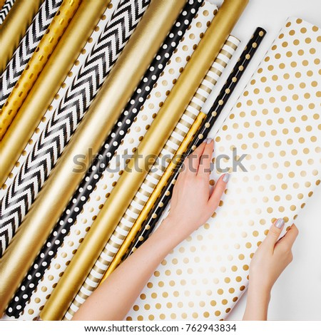 woman packing gift in gold paper with blank space on a white background for christmas