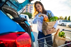 Woman packing shopping bags into a trunk of her car. Young woman with groceries at parking lot. Young women packing groceries from supermarket in car trunk. Woman holding groceries in reusable bag