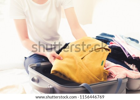 Woman packing travel bag for summer vacation. Tourism and objects concept, suitcase for summer holidays #1156446769