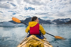 Woman paddle a canoe on an icy bay in Alaska exploring glaciers