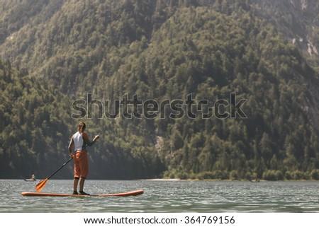 Woman Paddle boarding on a calm lake