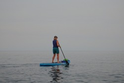 Woman Paddle Boarding on Blue Waters of Lake Tahoe with Smoke Filled Sky from 2020 WildfiresOLYMPUS DIGITAL CAMERA