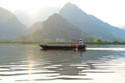Woman paddles fishing boat in Vietnam, evening sunshine light,  mountains reflecting in water. Vietnamese woman wearing traditional conical hat rowing boat in sunset light