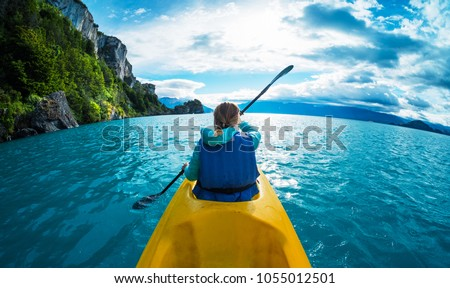 Woman paddles kayak in the lake with turquoise water. Patagonia, Chile