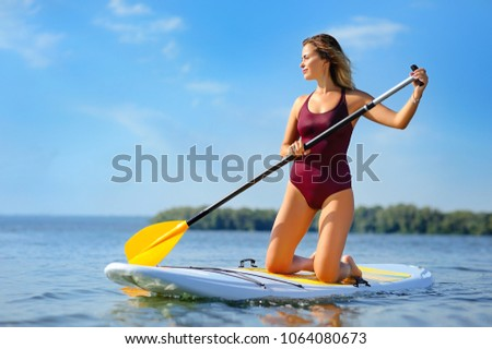 Woman paddling along the river standing on her knees on the sup board