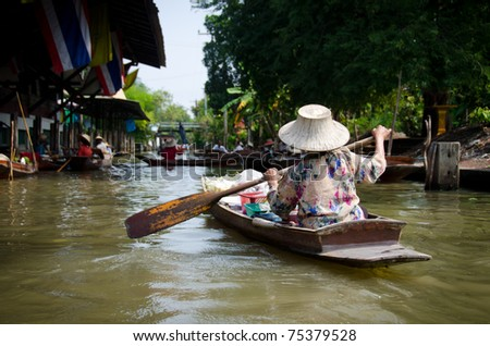 Woman paddling in the floating market in Thailand