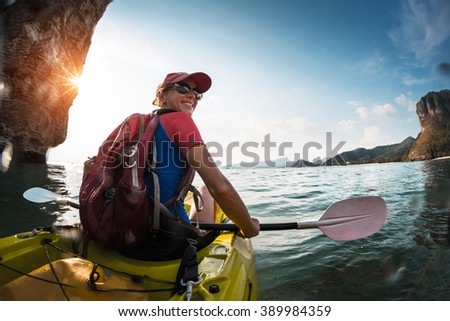 Woman paddling the sea kayak in the tropical calm lagoon with mountains