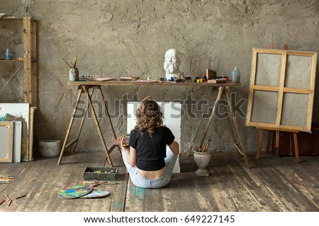 Woman painter sitting on the floor in front of an empty canvas and drawing. Art studio interior. Horizontal background. Drawing supplies, oil paints, artist brushes, canvas, frame. Creative concept #649227145