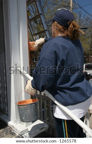 woman painting exterior of house