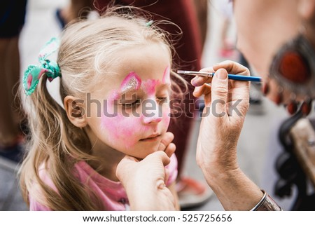 woman painting face of kid outdoors. baby face painting #525725656