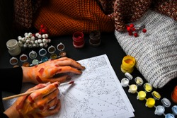 woman painting. hands painted. Picture by numbers. Drawing on canvas. Male hand with brush. Numbered paint cans. Creative hobby. Painting for beginners. Novice artist. Art idea.Brushes and paints