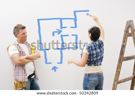 Woman painting new ground plan on apartment wall, man looking with arms folded, smiling.