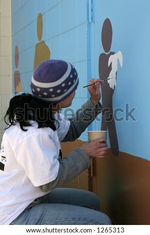 woman painting pictures on exterior of building