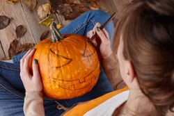 Woman painting pumpkin face and making jack latern for Halloween