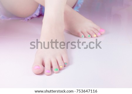 Woman painting toe nails own with manicure multi colored Nail Polish gel. fingernail paint,colorful in the bottle for beautiful feet . Customise sweet candy pastel bright colors tone .