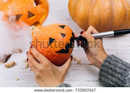 Woman paints a face on a little orange pumpkin for Halloween