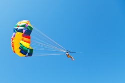 woman parasailing on parachute in blue sky in summer day