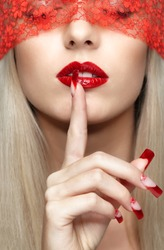 Woman part of face with eyes closed by red ribbon and with red french acrylic nails manicure
