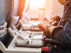 woman passengers eats lunch in travel aboard of international flight