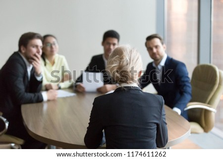 Woman passing job interview at office. Candidate sitting her back to camera. On a background black boss, director holding resume paper and young multiracial colleagues. Interview, hiring, hr concept