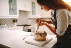 Woman pastry chef decorating chocolate cake in the kitchen. Female wearing a apron decorating cake with a pastry bag with cream.