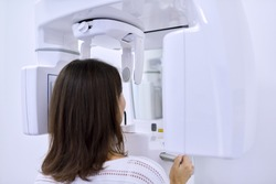 Woman patient in dental x-ray machine, back view. Modern dental diagnostic equipment, panoramic radiography, medical technology