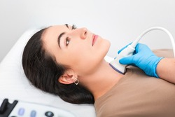 Woman patient receives thyroid diagnostics. Treatment of thyrotoxicosis, and hypothyroidism. Ultrasound diagnostics of the endocrine system and thyroid