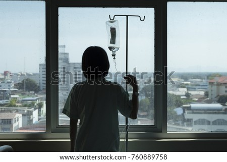 Woman  Patient stand at window with saline solution stand and feel Depressive Illness  dark in hospital room