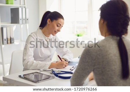 Woman patient visiting female doctor at clinic office. Medical work writes a prescription on a table in a hospital.