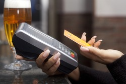 Woman pay with credit card in bar