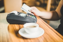 Woman pay with credit card in cafe bar good background
