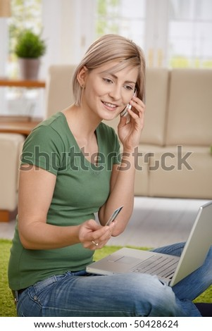 Woman paying bills from home with credit card, laptop and mobile phone.