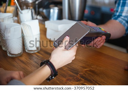 Woman paying for coffee by mobile phone and using reader holded by waiter in cafe #370957052
