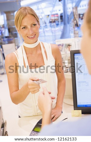 Woman paying in store with credit card