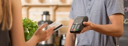 Woman paying with a debit card in a restaurant, waitress holding a payment terminal