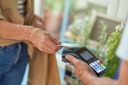 Woman paying with bank card in shop