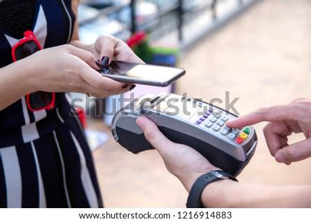 Woman payment via credit card swipe machine.