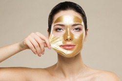 Woman peel off Gold Facial Mask. Collagen Golden Anti Aging Wrinkle Lifting Mask. Spa Beauty Treatment