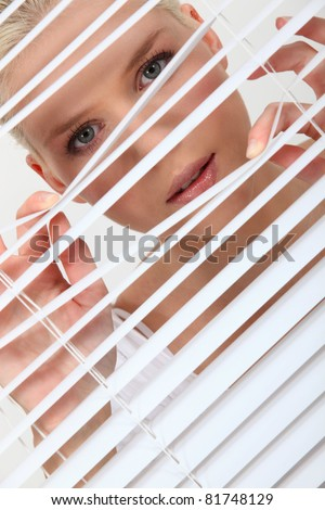 Woman peering through some blinds