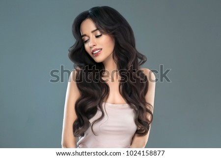 Woman perfect hair beautiful female portrait over blue background. Brunette haircare long curly hairstyle beauty concept