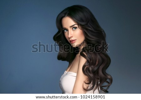 Woman perfect hair beautiful female portrait over blue background. Brunette haircare long curly hairstyle beauty concept #1024158901