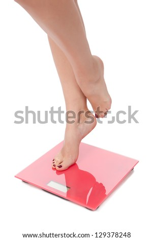 Woman perfect shaped legs on scale on white background
