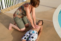 Woman performing cardiopulmonary resuscitation, known as car, on a young boy child who was in a state of medical emergency when he inhaled water while swimming at a swimming pool.