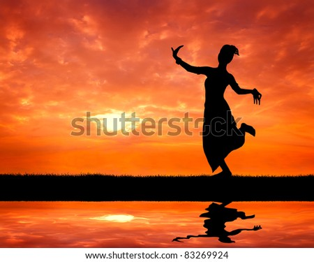woman performing typical thai dance at sunset silhouetted