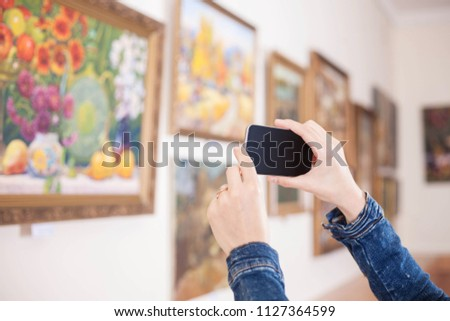 Woman photograph a painting at an exhibition of the art gallery.